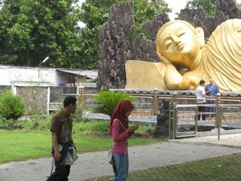 Young Muslim couple taking a stroll through the park of a Buddhist Monastery (Maha Vihara Trowulan) in East Java.