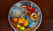 <p>A <em>pūjeca tāṭ</em>. The contents of this plate – incense sticks, marigold flowers, an oil lamp, sugar, gulal, kumkum, turmeric powder, and rice – are used during ritualistic ceremonies to worship a deity.<br /><br />Photo: Kalindi Kokal, Paaj Pandhari, Maharashtra, India, 2015<br />Max Planck Institute for Social Anthropology</p>