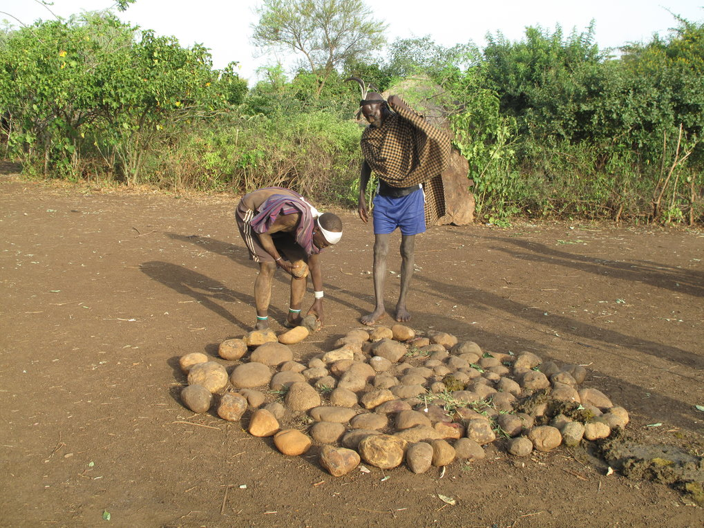 Mela men adding a ring of stones to a stone platform at a komorut's homestead, Mela, Ethiopia, 2013